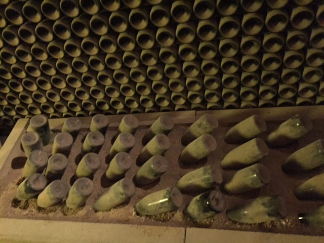 Botellas pinchadas en arena para depositar las levaduras en el cuello.